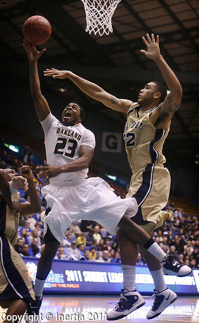 SIOUX FALLS, SD - MARCH 8: Reggie Hamilton #23 of Oakland scoops a shot under the defense of Damen Bell-Holter #32 from Oral Roberts during the first half of the 2011 Summit League Championship game Tuesday night in Sioux Falls, SD. (Photo by Dick Carlson/Inertia)