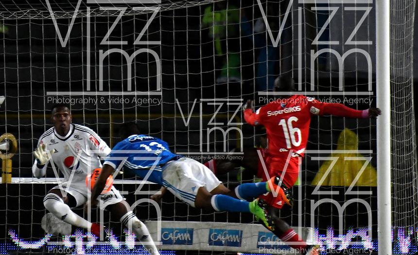BOGOTA - COLOMBIA - 11 - 03 - 2017: Harold Mosquera (Cent.), jugador de Millonarios, anota gol a Carlos Bejarano (Izq.), portero de America, durante partido de la fecha 9 entre Millonarios y America de Cali, por la Liga Aguila I-2017, jugado en el estadio Nemesio Camacho El Campin de la ciudad de Bogota. / Harold Mosquera (C) player of Millonarios scored a goal to Carlos Bejarano (L), goalkeeper of America, during a match between Millonarios and America de Cali, of the date 9 for the Liga Aguila I-2017 played at the Nemesio Camacho El Campin Stadium in Bogota city, Photo: VizzorImage / Luis Ramirez / Staff.