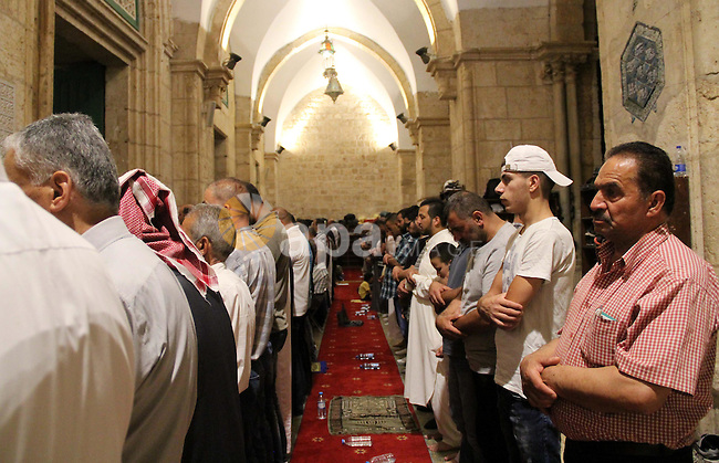 """Palestinian Muslim worshippers perform """"Taraweeh"""", nightly prayer of the month of Ramadan, in front of the Dome of the Rock mosque, in Jerusalem's old city on June 21, 2016. Ramadan is sacred to Muslims because it is during that month that tradition says the Koran was revealed to the Prophet Mohammed. The fast is one of the five main religious obligations under Islam. More than 1.5 billion Muslims around the world will mark the month, during which believers abstain from eating, drinking, smoking and having sex from dawn until sunset. Photo by Mahfouz Abu Turk"""