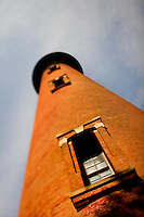 The Currituck Beach Lighthouse, one of the few North Carolina coastal lighthouses that visitors can climb to the top, is located on the Outer Banks in Corolla, North Carolina. With its red brick exterior, the lighthouse is  an example of Gothic Revival architecture. Located in the town of Corolla, the Currituck Beach Light was the last of four beacons placed at intervals from Cape Henry, Virginia to Cape Hatteras. Like other lighthouses on the North Carolina coast, the Corolla Lighthouse / Currituck Beach Lighthouse still aids ships in navigation. Charlotte NC photographer Patrick Schneider has extensive photo collections of the following lighthouses: Bodie Island Lighthouse, Bald Head Island Lighthouse, Cape Fear Lighthouse, Cape Hatteras Lighthouse, Cape Lookout Lighthouse, Currituck Beach Lighthouse, Diamond Shoal Lighthouse, Federal Point Lighthouse, Oak Island Lighthouse, and Ocracoke Lighthouse on Ocracoke Island.