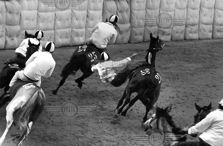 © Francesco Cito / Panos Pictures..Siena, Tuscany, Italy. The Palio. ..A jockey falls off his horse during the 'Tratta', when horses are assessed and selected before the main race...Twice each summer, the Piazza del Campo in the medieval Tuscan town of Siena is transformed into a dirt racetrack for Il Palio, the most passionately contested horse race in the world. The race, which lasts just 90 seconds, has become intrinsic to the town's heritage since it was first run in 1597...