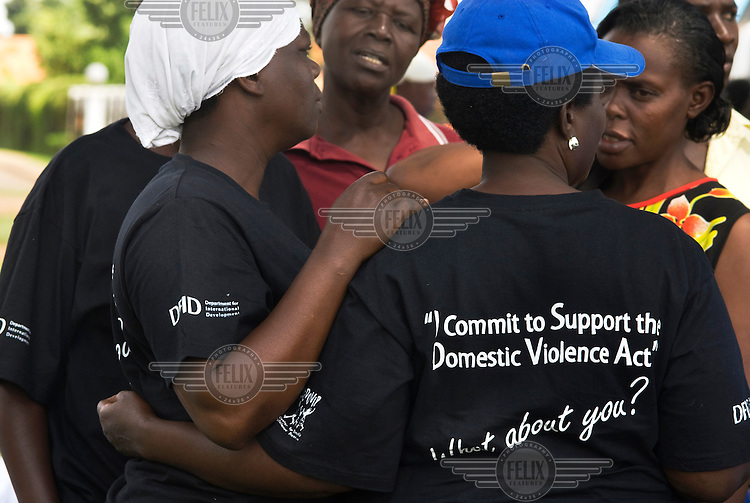 Procession to Parliament to mark 16 days of action on sexual and gender based violence. A group of women wear DFID (UK Department for International Development) T-shirts with the slogan 'I commit to support the domestic violence act'.