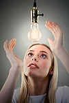 Young blonde woman looking up at light bulb, hands raised