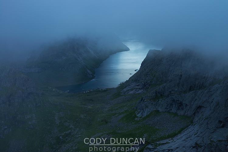 Clouds conceal mountain peaks over Kirkefjord from summit of Breiflogtind, Moskenesøy, Lofoten Islands, Norway
