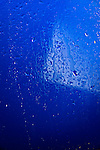 Abstract blue wet glass with drops of water background texture