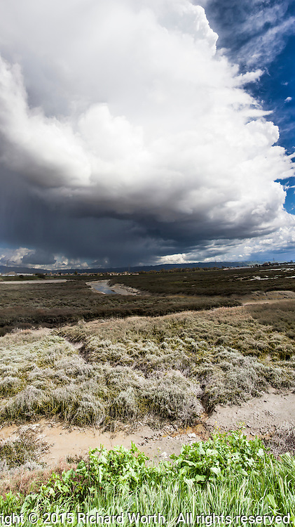 A storm cloud moves over the East Bay toward San Francisco Bay, converting the weather from sunny to cloudy and then rainy.