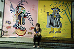 A woman sits in front of the colorfully decorated shutters of a variety goods store in Shimokitazawa, Setagaya Ward, Tokyo, Japan..Photographer: Robert Gilhooly