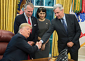 "United States President Donald J. Trump, left, shakes hands with US Senator Sheldon Whitehouse (Democrat of Rhode Island),right, prior to signing S. 3508, the ""Save Our Seas Act of 2018"" in the Oval Office of the White House in Washington, DC on Thursday, October 11, 2018. Looking on are US Senator Dan Sullivan (Republican of Alaska), center left, and Julie Fate, wife of Senator Sullivan, center right.<br /> Credit: Ron Sachs / CNP"