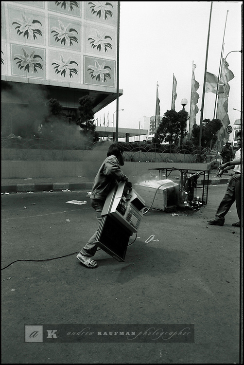 Summer '98-- Jakarta, Indonesia -- A rioter puts a cash register on a fire to protest against fuel hikes imposed by President Suharto..