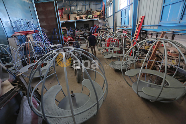 """Palestinian men work on the manufacture and maintenance of the swings """"amusement games"""" at al-salam factory in the Zeitoun neighborhood, in Gaza city, on November 26, 2016. Israeli occupation prevented of the introduction of large amounts of material """"Fiber Glass"""" which makes them the swings, leading to high prices and stop a large number of factories for work. Photo by Mohammed Asad"""