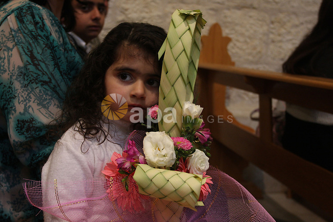 """Palestinians Catholic attend a Palm Sunday at a church """"Nativity"""" in Bethlehem in the West Bank in, Sunday, April 1, 2012. Palm Sunday commemorates Jesus Christ's triumphant entry into Jerusalem when his followers laid palm branches in his path, prior to his crucifixion.  Photo by Issam Rimawi"""