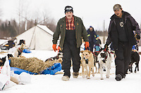 Checkpoint volunteers, John Runkle (L) and Steven Nikolai Jr., park John Baker's dogs at the Nikolai checkpoint on Tuesday during Iditarod 2008