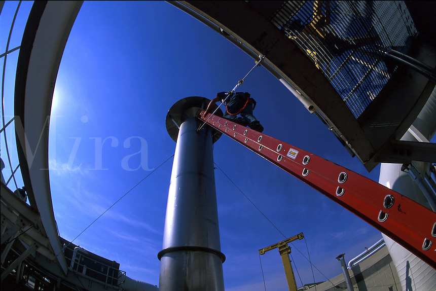 Workman on a ladder installing a deflector cap on an exhaust stack at a food processing plant. Tennessee.