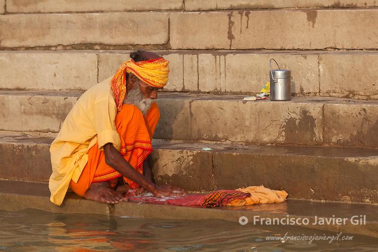 Pilgrim at ghat steps on river Ganges, Varanasi, Uttar Pradesh, India