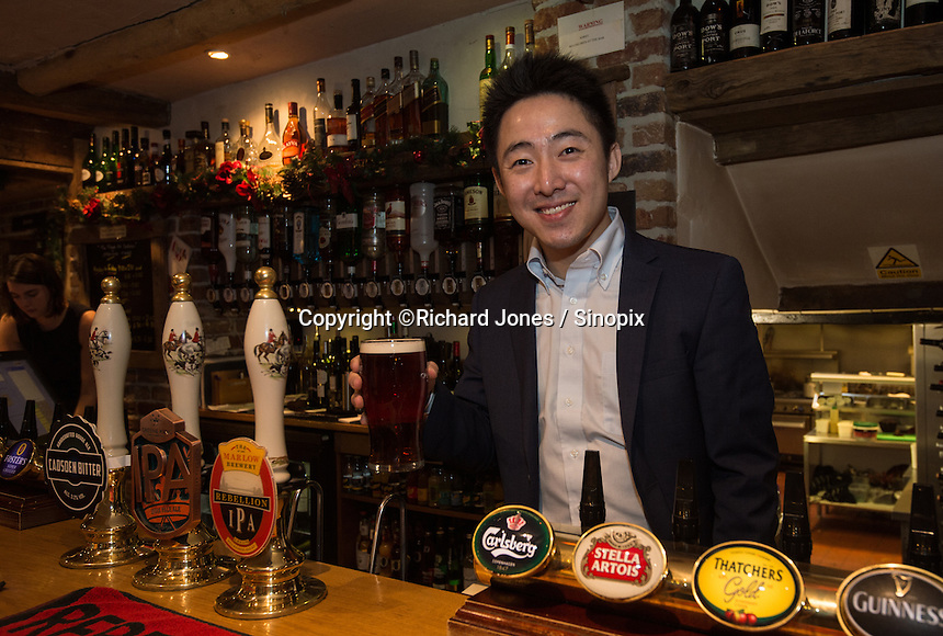 Peter Zhang, Managing Director, SinoFortone Group behind the bar at the The Plough at Cadsden, Buckinghamshire. The group bought the pub after it was visited by Chinese Premiere Ji Jinping last year, and aim to develop  a chain of English-style pubs China.<br /> <br /> Photo by Richard Jones