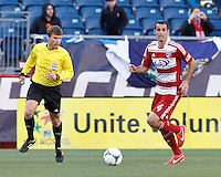 FC Dallas midfielder Andrew Jacobson (4) brings the ball forward. .  In a Major League Soccer (MLS) match, FC Dallas (red) defeated the New England Revolution (blue), 1-0, at Gillette Stadium on March 30, 2013.