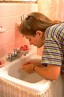 Girl age 13 washing her face in bathroom at home.  St Paul Minnesota USA