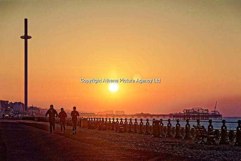 Three joggers make the most of the morning as the sun rises over Brighton Pier a freezing cold but clear morning  in East Sussex, England UK. Saturday 24 February 2018