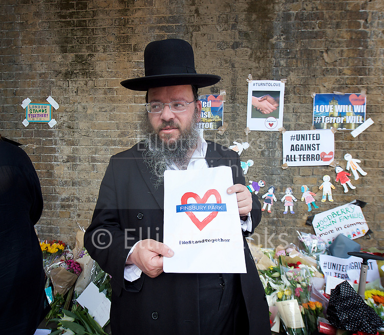 Floral Tributes and messages left outside the Finsbury Park Mosque, Finsbury Park, London, Great Britain <br /> 20th June 2017 <br /> <br /> Hanaja Fischer from the Jewish Stamford Hill community holds a We Stand Together sign outside the Mosque <br /> <br /> following a terror attack outside  the Muslim Welfare House of Seven Sisters Road early hours of 19th June 2017 <br /> <br /> Photograph by Elliott Franks <br /> Image licensed to Elliott Franks Photography Services