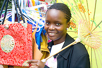 African American woman shows items at Hennepin Technical College booth. Dragon Festival Lake Phalen Park St Paul Minnesota USA