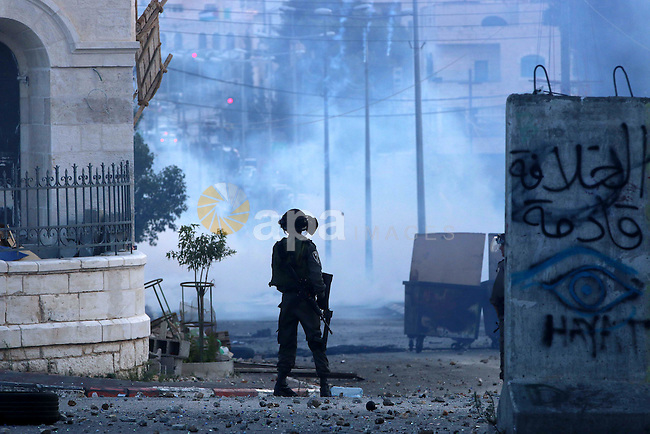 A member of Israeli security forces fires tear gas towards Palestinian protesters during clashes in the West Bank town of Bethlehem on October 9, 2015. Tension and protests rose after an Israeli man on 09 October stabbed four Palestinians in southern Israel, in what is being seen as a revenge attack, officials said. On 08 October several violent incidents happened, including stabbings which left eight Israelis injured, one Palestinian was killed in East Jerusalem and six in the Gaza Strip in clashes with the army while at least six were injured on the West Bank. Photo by Muhesen Amren