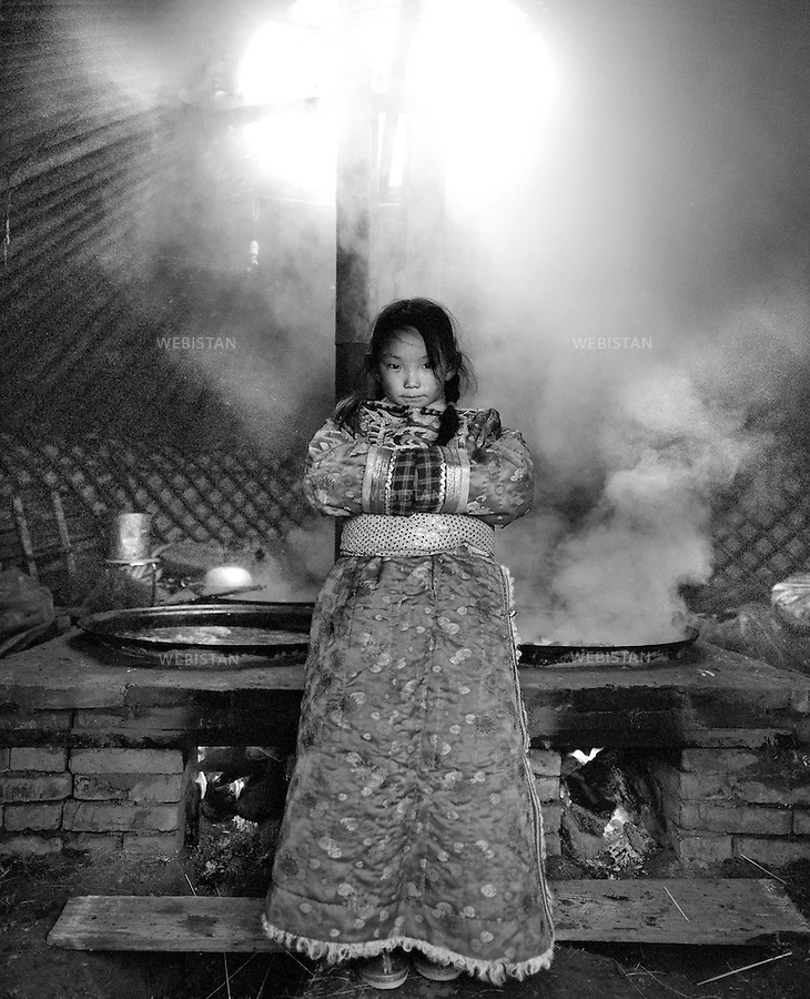 Inner Mongolia, Xilingol Meng, East Ujimqin Qi, Wulagai Sumu, Hadatu Gacha, December 2006.Aoyunsudu (age 10)...Standing in the yurt where some meat is being braised for the celebration of her grandmother's 73rd birthday..Whenever there are celebrations on the pastoral grasslands, children are always very excited. They could put on new dresses and running, chasing on the grassland. Aoyunsudu studies 1st class of 3rd grade of East Ujimqin Mongolian school, and she is the monitor of her class. She is always on the list of the first ten students who succeed in exams. She likes singing, dancing and also has talent in painting..
