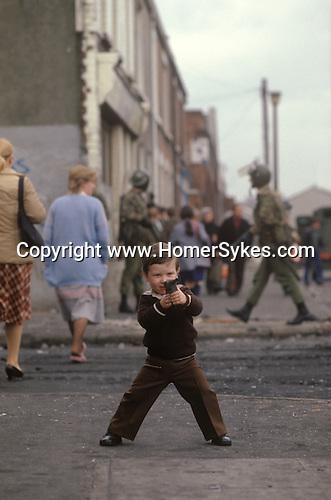 Ireland The Troubles. Belfast young boy with toy gun. British soldier patrols street behind. Downtown urban shopping street Belfast. 1980s