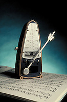 Metronome standing on sheet music.  May not be used in an elementary school dictionary.