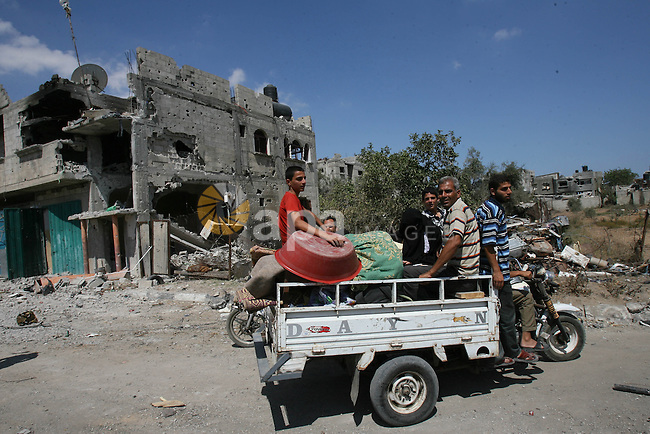 Palestinians ride on a motorbike rickshaw as they return to their houses during an humanitarian truce  in Khan Younis in the southern Gaza Strip on July 26, 2014. Palestinians retrieved dozens of bodies from the rubble of Gaza homes during a brief truce in the fighting, raising to over 900 the overall death toll of Israel's onslaught on the territory since July 8, medics said. Photo by Eyad Al Baba