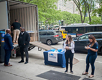 Workers for Roadway Moving attempt to cajole passer-by in Midtown in New York into receiving a free 10 minute massage at a branding event on Wednesday, May 10, 2017. May is National Moving Month and Roadway is attempting to de-stress those moving with the massages, as well as promoting themselves. (© Richard B. Levine)