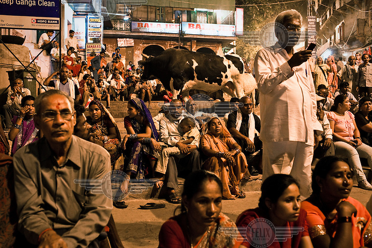 Some take photos using mobile phones while other pilgrims look on while they attend the evening prayers at the Dashashwamedh Ghat in the ancient city of Varanasi.