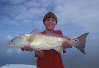 Boy with a large Redfish (Red Drum) he caught in the Everglades, Florida Keys.