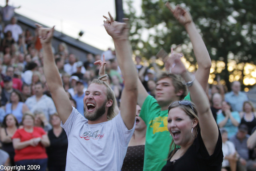 Travis Bouwman, left, and Heather Langeland, both of Sumas, cheer for the band Foreigner at the NW Washington Fair on August 20, 2009. Photo by Meryl Schenker.