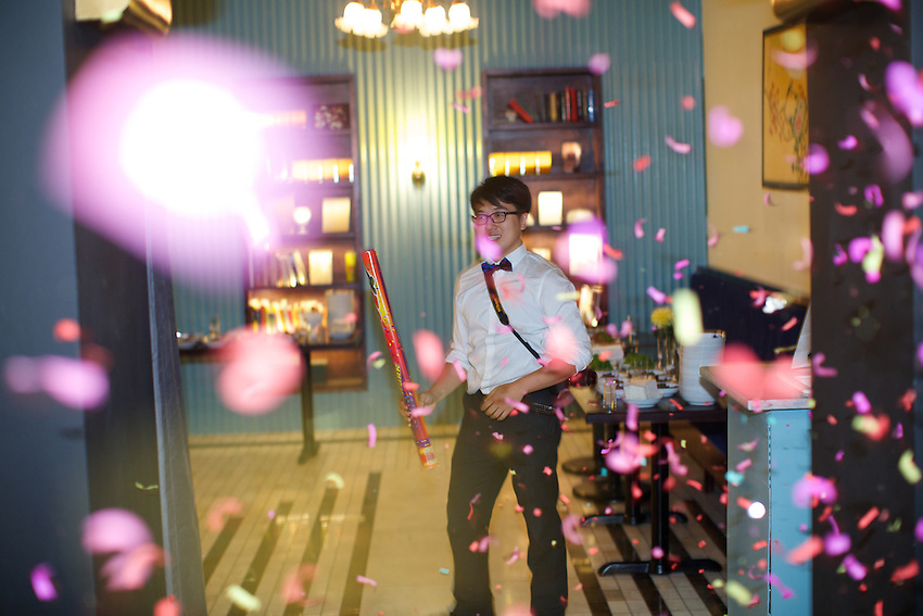 New York, NY - September 8, 2014:  Waiter sets off confetti popper during a special dinner at China Blue in Tribeca. The dinner, which took place during the Chinese Mid-Autumn Festival, centered on &quot;Weird Foods&quot; that Westerners don't often try.<br /> <br /> CREDIT: Clay Williams for Gothamist.<br /> <br /> &copy; Clay Williams / claywilliamsphoto.com