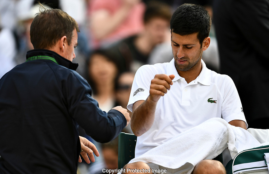 Novak Djokovic (SRB) receives treatment on court