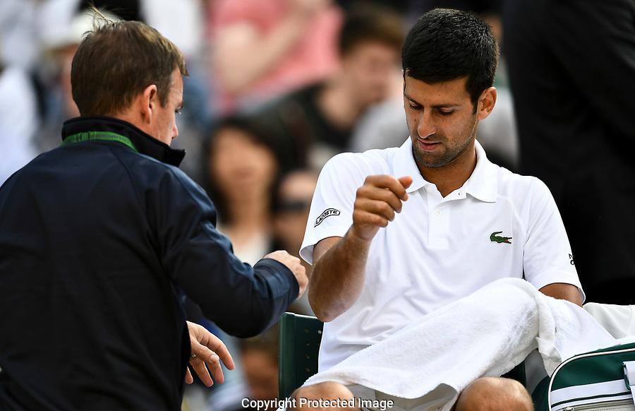 Novak Djokovic (SRB) receives treatment on court