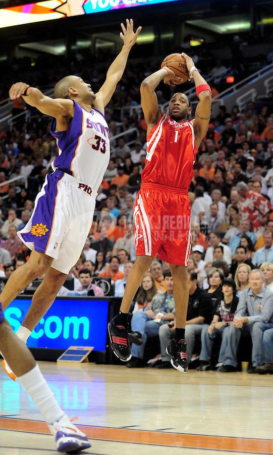 Mar. 22, 2008; Phoenix, AZ, USA; Houston Rockets guard (1) Tracy McGrady shoots under pressure from Phoenix Suns forward (33) Grant Hill at the US Airways Center. Mandatory Credit: Mark J. Rebilas