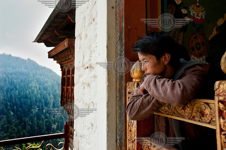 A man alooks out from a room housing a prayer wheel at the Tango Dzong Monastery.