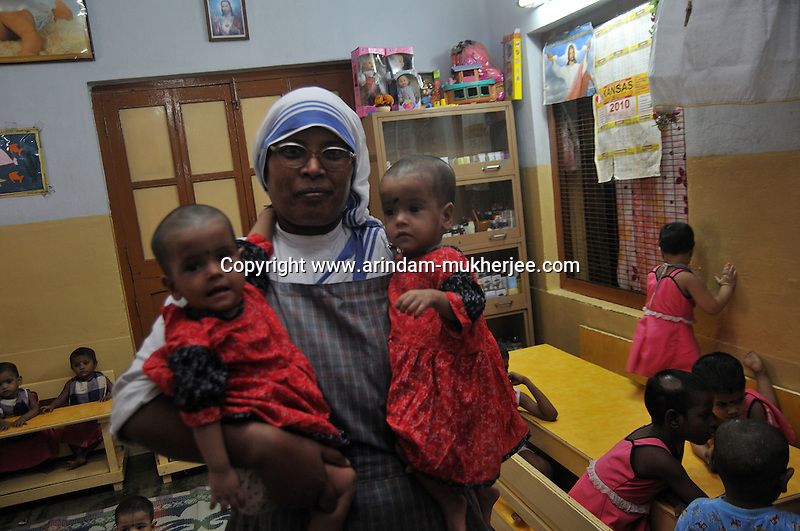 A sister holding a malnutrished twin at Sishu Bhavan, which is the house for children founded by Mother Teresa.  Kolkata, West Bengal, India. 18th August 2010. Arindam Mukherjee