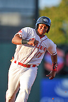 Third baseman Rafael Devers (13) of the Greenville Drive rounds third base, heading for home in a game against the Augusta GreenJackets on Thursday, July 16, 2015, at Fluor Field at the West End in Greenville, South Carolina. Devers is the No. 6 prospect of the Boston Red Sox, according to Baseball America. Greenville won, 11-5. (Tom Priddy/Four Seam Images)