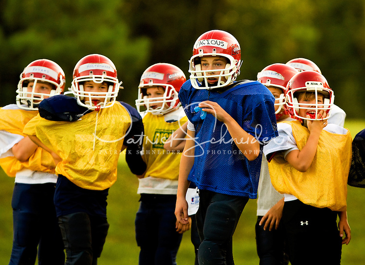 Each fall football season, youths across the United States pull on helmets and strap on pads to play American football, one of the country's most popular sports. The Pop Warner football league has been helping youngsters play the sport since 1929. Photo is part of a series of images documenting one team of North Carolina boys learning and playing the sport in Cornelius, NC in fall 2009. They're playing in the Lake Norman Giants league.