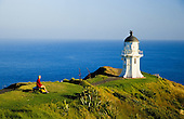 A tourist sits and admires the Cape Reinga lighthouse at the northern most tip of New Zealand. Northland, New Zealand.