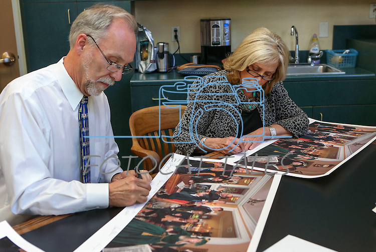 """Historian Ron James and former first lady Dema Guinn sign prints of Steven Saylor's """"Nine Cheers for the Silver State"""" artwork, at the Capitol, in Carson City, Nev., on Wednesday, Sept. 24, 2014. Dignitaries featured in the painting will sign the 150 limited edition prints which will be sold as a fundraiser for the Comstock Foundation for History and Culture.<br /> Photo by Cathleen Allison"""