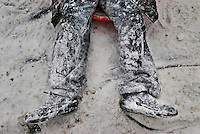 The legs of a sledder are blanketed with wet snow at the end of a run.