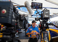 Oct 17, 2015; Ennis, TX, USA; NHRA funny car driver Ron Capps is surrounded by cameras as he films a commercial in the pits during qualifying for the Fall Nationals at the Texas Motorplex. Mandatory Credit: Mark J. Rebilas-USA TODAY Sports