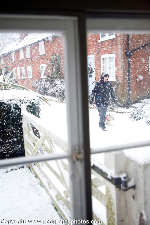 View through window of heavy snow falling in village street with woman walking her dog