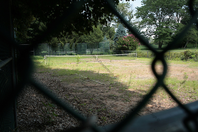 Stock Photo looking through the fence at an old unmaintained clay tennis court.