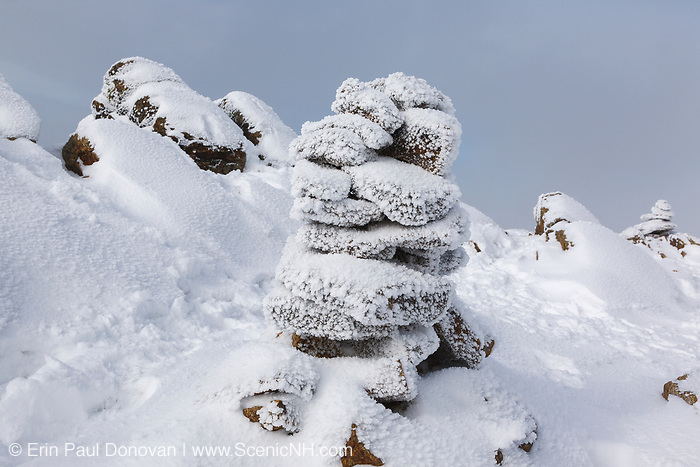 Snow covered rock cairn on the summit of Mount Liberty in the White Mountains, New Hampshire during the winter months.