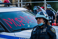 NEW YORK, NEW YORK - MAY 30: A police officer stands next to a painted car during the protest in response to the police officer who killed George Floyd in Brooklyn on May 30, 2020 in New York. The protests spread across the country in at least 30 cities in the United States. United States For the death of unarmed black man George Floyd at the hands of a police officer, this is the latest death in a series of police deaths of black Americans (Photo by Pablo Monsalve / VIEWpress via Getty Images)