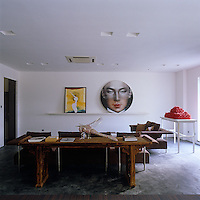Gallery owner Fabien Fryns' contemporary office juxtaposes an antique Chinese table with modern sofas, with a painting by Schnabel on the left and a portrait by Ling Jians Tondo on the right, while a sculpture Planet of the Ants by Ma Hans is displayed by the window